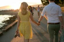 couple walking on seawall at sunset engagement photos