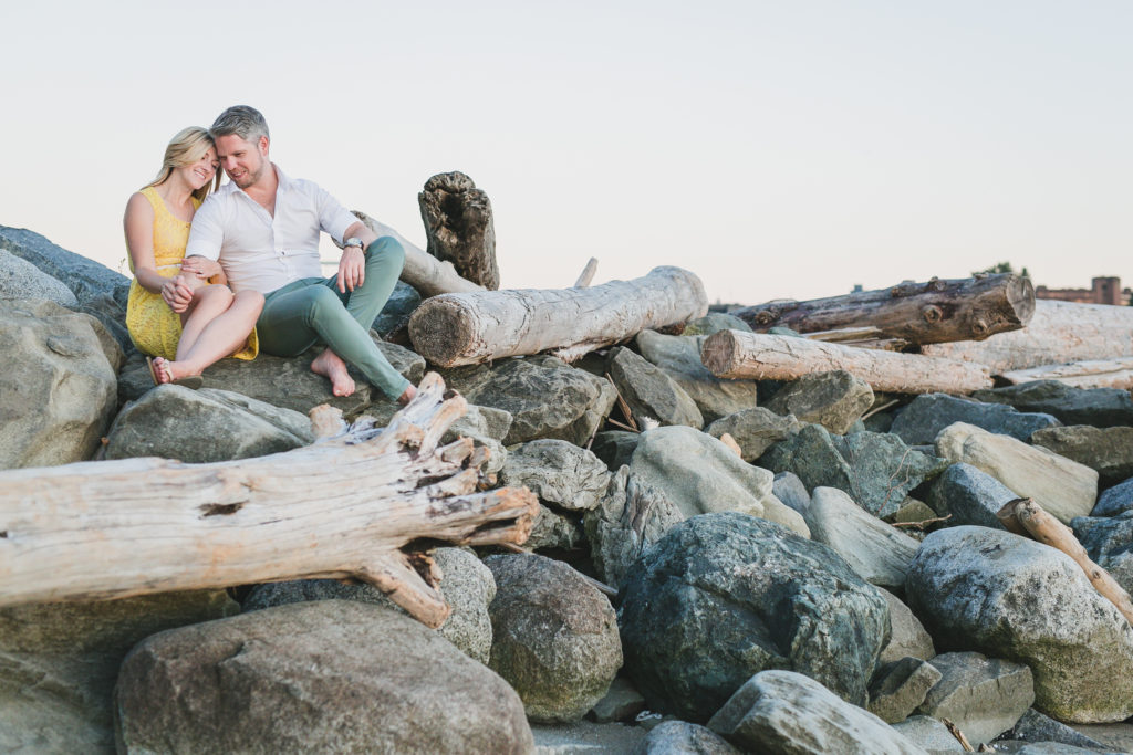 english bay vancouver engagement photos on driftwood and rocks