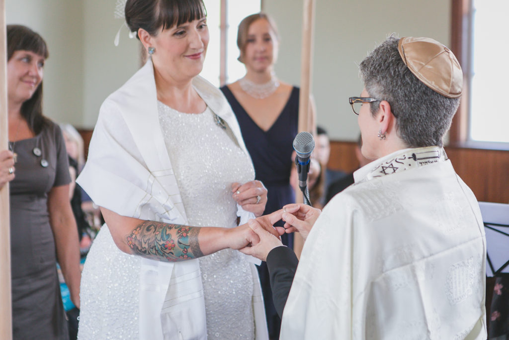 exchanging rings at same-sex jewish wedding ceremony vancouver, tattooed bride